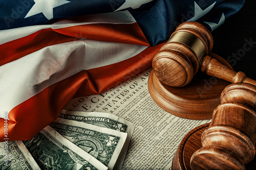 Fotografia Wooden judge mallet with Dollars notes on the USA flag with Declaration of Indep
