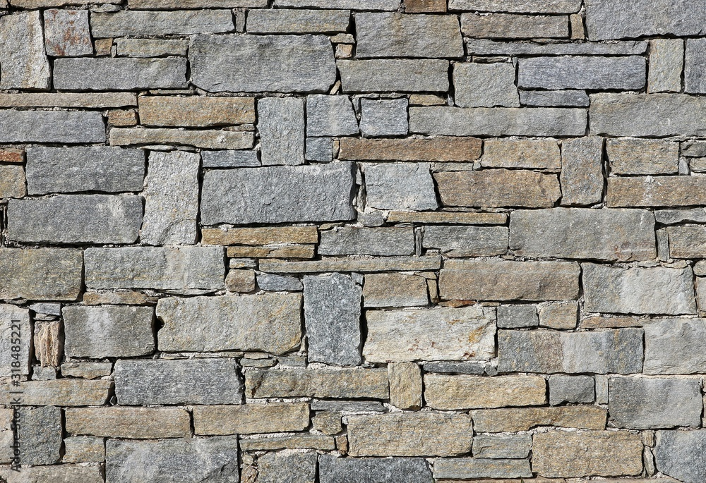 Fototapeta Stone wall made from irregular shaped natural rocks. The colors are gray and brown. Masonry. Background and texture
