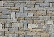Stone wall made from irregular shaped natural rocks. The colors are gray and brown. Masonry. Background and texture