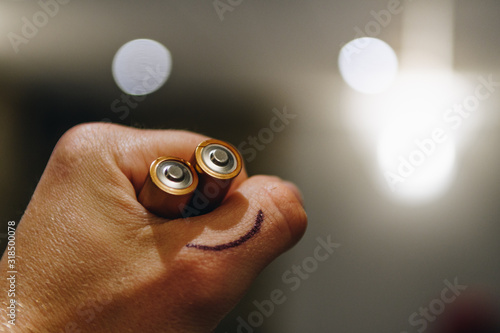 Obraz Cropped Hand Of Person Holding Batteries With Smiley Face - fototapety do salonu