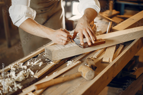 Stampa su Tela Man working with a wood. Carpenter in a white shirt