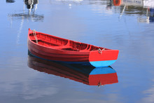 RED BOAT MOORED IN WATER