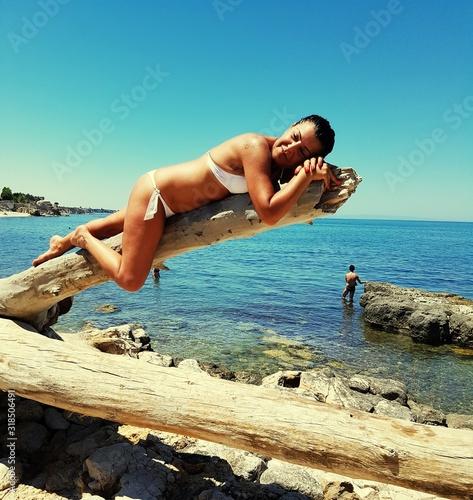 Woman Relaxing Against Sea At Beach - fototapety na wymiar