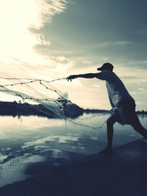MAN Casting A Net DURING SUNSET
