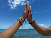 Cropped Hands Of Friends High Fiving Against Sea And Sky