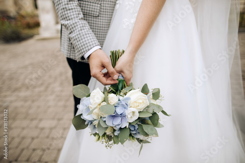 Fotomural Beautiful wedding bouquet in the hands of the bride and groom