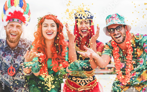 Happy dressed people celebrating at carnival party throwing confetti - Young friends having fun together at fest event - Youth, hangout, festive and happiness concept - Focus on left couple hands - 318517674