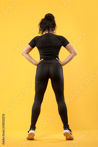 Size plus woman sporty fit woman in sportswear, athlete makes fitness exercising on yellow background Wallpaper Mural
