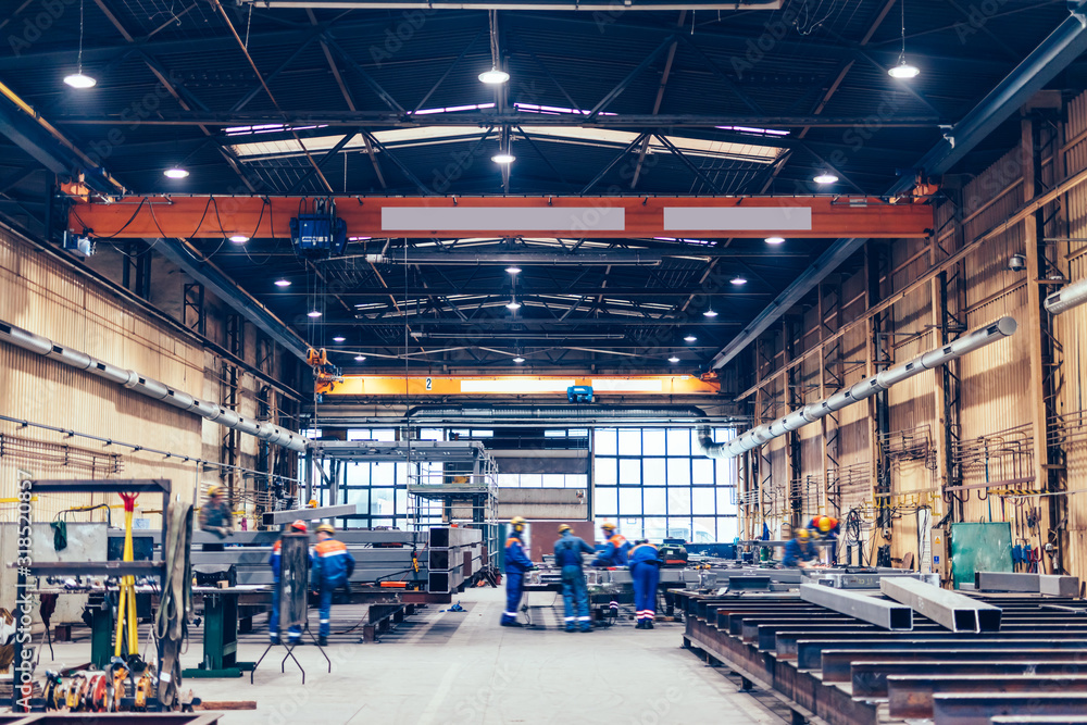 Fototapeta Large factory hall, blue-collar workers at work.
