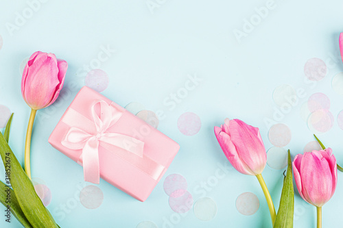 Fototapeta View from above tulips and gift box with copy space on blue. Background for womens day, 8 March Valentine's day, 14 february. Flat lay style, top view, mockup, template, overhead. Greeting card obraz na płótnie