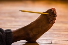 Low Section Of Man Holding Pencil With Toes
