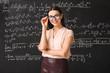 Female teacher near blackboard in classroom