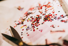 Close-Up Of Sequins With Scissor On Table