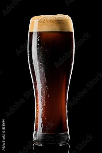 Valokuva Stange beer glass with black stout covered with drops and froth studio shot on black background