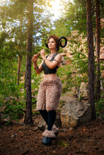 A Girl In The Image Of A Faun Stands With A Wooden Flute. Model With Horns On His Head And With Furry Pants In The Woods Among The Stones