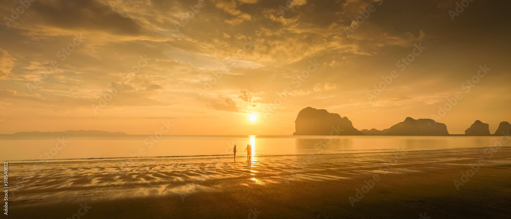 Fototapeta view seaside evening of tourists walking relax on sand beach with mountain and yellow sun light and cloudy sky background, sunset at Pak Meng Beach, Trang Province, southern of Thailand.