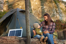 Mother Smiling To Child, Sitting On A Log In The Forest Near Tourist Solar Panel And A Tent Camp. Woman Is Holding A Telephone. Family Weekend In The Warm Autumn Evening Outdoor