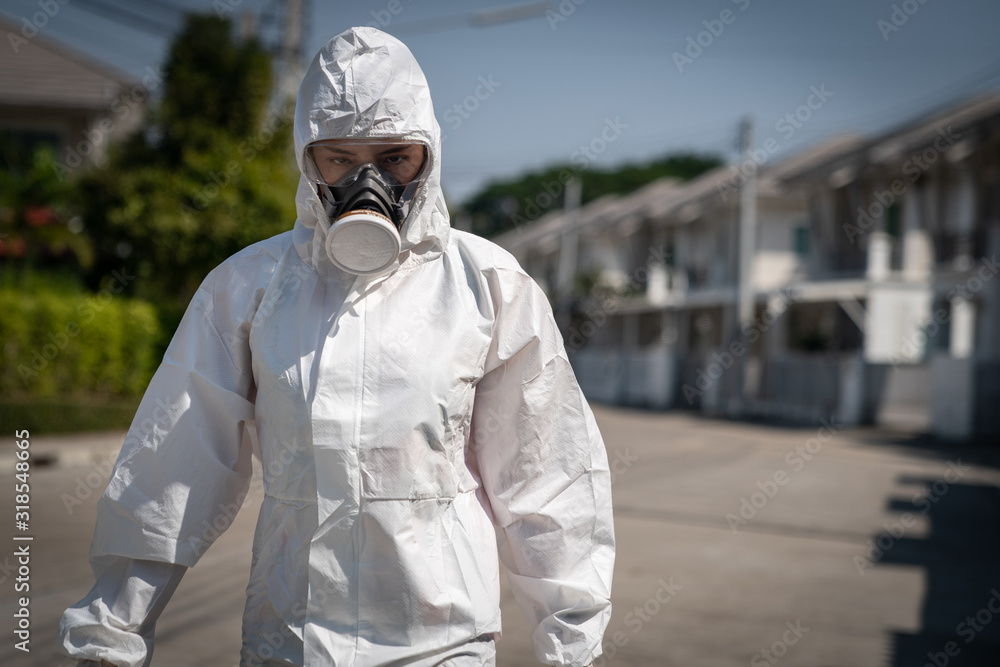 Fototapeta Woman wearing gloves with biohazard chemical protective suit and mask. She crossed her arms with unhappy face.