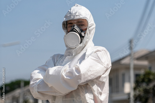 Fototapeta Woman wearing gloves with biohazard chemical protective suit and mask