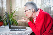 canvas print picture - Old lady having a pleasant skype call on her laptop