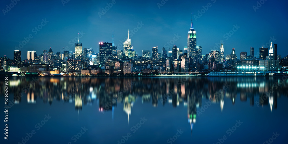 Fototapeta Panorama of the skyline of Manhattan viewed from Jersey city during the blue hour. New York skyline at night with reflections.