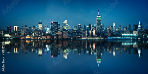 Fototapeta Panorama of the skyline of Manhattan viewed from Jersey city during the blue hour. New York skyline at night with reflections. obraz