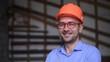 Building constructor engineer wearing orange helmet at the working site smiling towards camera