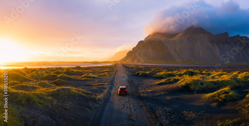 Fotografiet Gravel road at sunset with Vestrahorn mountain and a car driving, Iceland