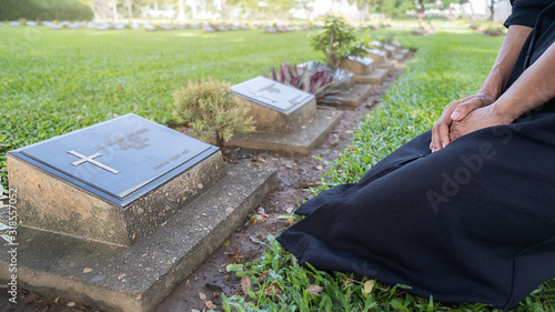 Mourning young woman kneeling at her family grave in beautiful green cemetery Canvas Print