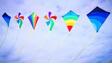 Low Angle View Of Colorful Kites Flying Against Cloudy Sky