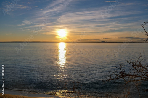 Romantic, dramatic winter sunset over the calm sea. Sunlight reflects on the small boat and on the water in the bay. Fantastic colors of the sky. Natural gradient. Roses, Catalonia, Spain.
