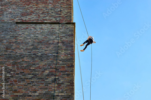 Young woman in silhouette, abseiling from a large old tower against a blue sky Canvas Print