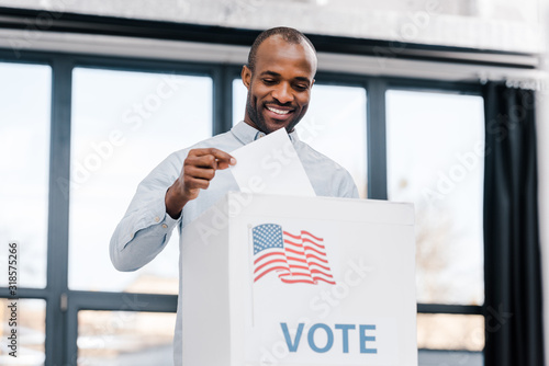Fotografie, Obraz happy african american man voting and putting ballot in box with flag of americ