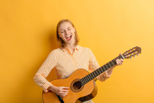 Portrait Of Young Caucasian Attractive Musician Woman In Casual Shirt, Singing With Opened Mouth. Young Female Artist Guitarist. Positive Woman With Musical Instrument Isolated Over Yellow Background