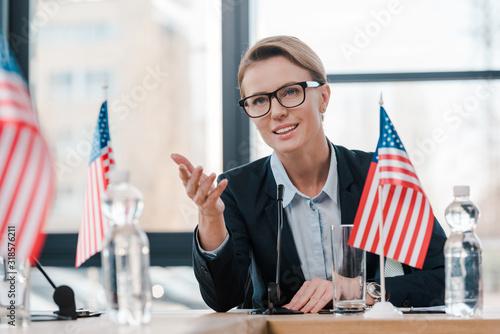 smiling diplomat in eyeglasses gesturing while talking near microphone and ameri Wallpaper Mural