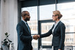 side view of attractive businesswoman shaking hands with african american businessman