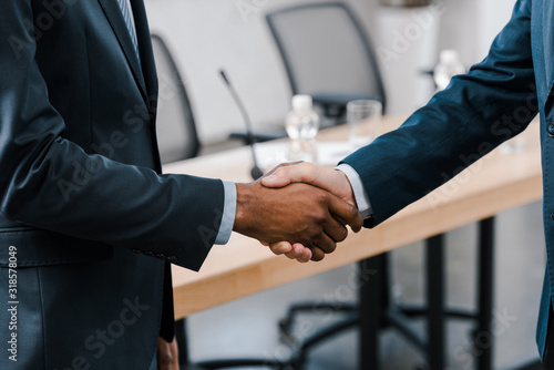 Fotografía cropped view of businessman shaking hands with african american diplomat