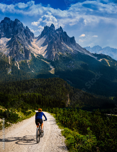 Tourist cycling in Cortina d'Ampezzo, stunning rocky mountains on the background Wallpaper Mural