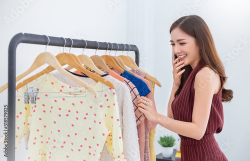 Fotografia Portrait of happy young beautiful asian girl choosing cloths in shopping mall or clothing store on sale