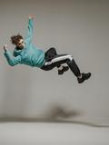 Boy dancing breakdance mid-air in studio. Acrobatic dancer.
