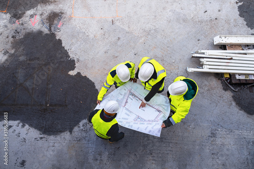 Obraz A top view of group of engineers with blueprints standing on construction site. - fototapety do salonu