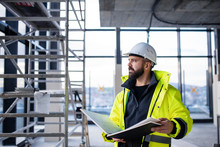 Man Engineer Standing On Construction Site, Holding Blueprints.