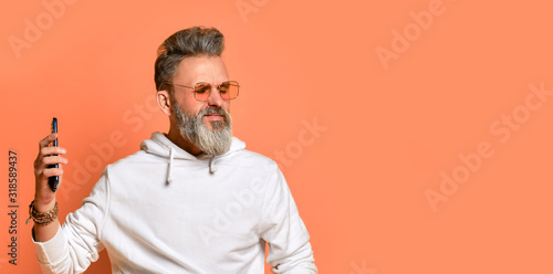 Stylish grey-haired hipster man in white hoodie and red sunglasses standing list Canvas Print