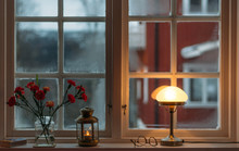 Illuminated Lamp By Vase On Window Sill