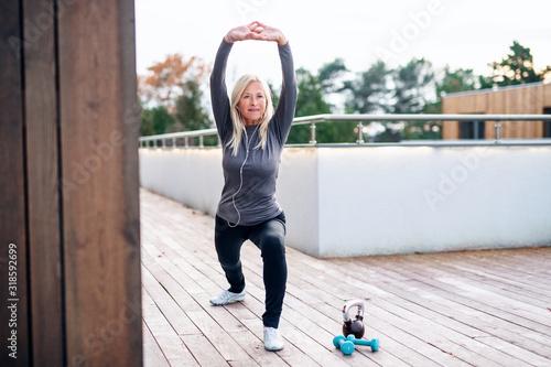 Obraz A senior woman doing exercise outdoors, stretching. - fototapety do salonu