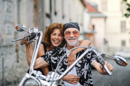 A cheerful senior couple travellers with motorbike in town. - 318593265