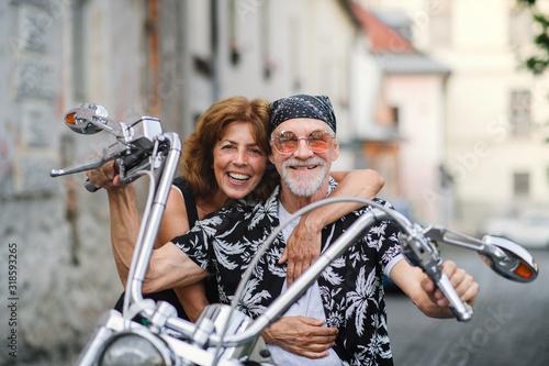 Rozochocona starsza para podróżuje z motocyklem w mieście.