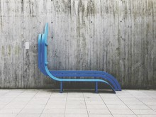 Empty Blue Bench At Footpath Against Wall