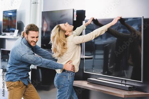 Cuadros en Lienzo angry boyfriend pulling girlfriend with tv in home appliance store