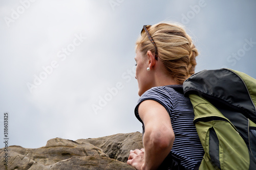 Fotografía  Low Angle View Of Young Woman Leaning On Rock Against Sky